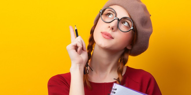 Redhead girl with notebook and pencil on yellow background.